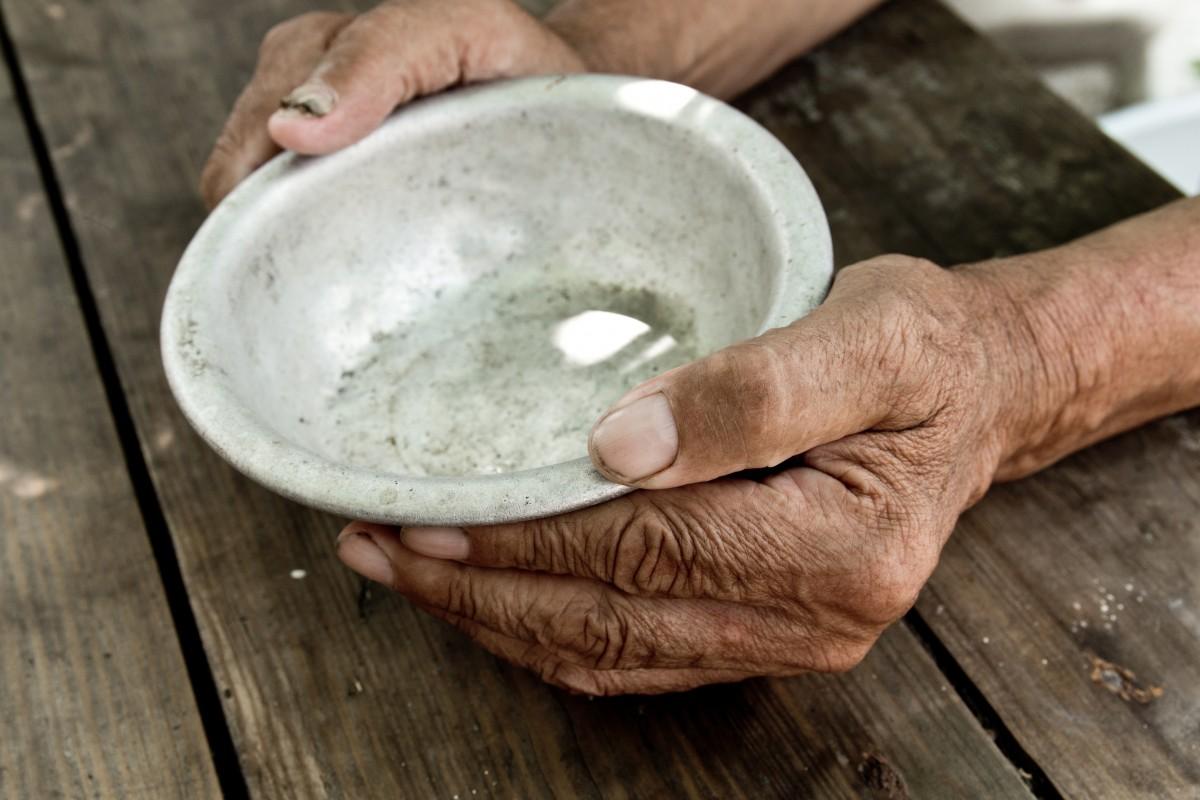 Man's hands around empty bowl.